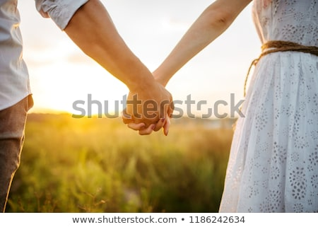 Stock photo: Image of beautiful young couple smiling and holding hands together while walking down city stairs