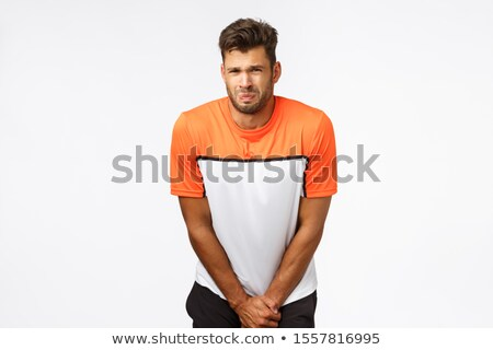Poor young sportsman, football player in sports t-shirt, bending and grab groin area as feeling pain Stock photo © benzoix