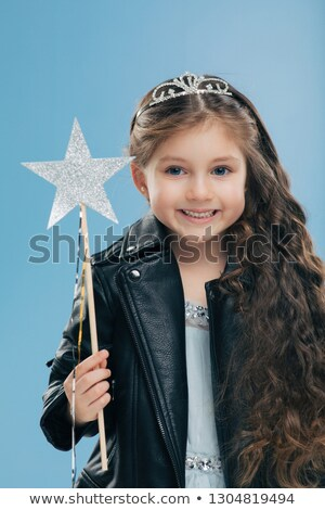 Satisfied small female child has long curly hair, dressed in black leather jacket, wears crown, hold Stock photo © vkstudio