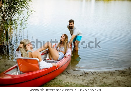 Young man pulling canoe into calm lake Stock photo © boggy