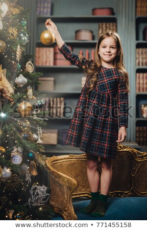 Pretty girl with charming smile stands on armchair, decorates Ne Stock photo © vkstudio