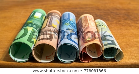 Stock photo: euro rolled bills and coin
