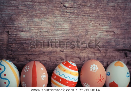 Stock photo: Group of colorful easter eggs decorated with flowers made by decoupage technique, in a basket on lig