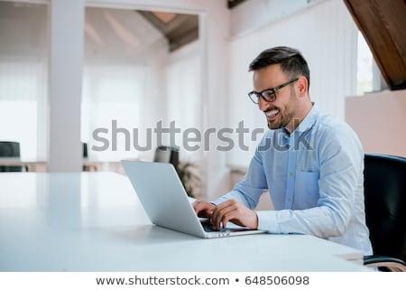 człowiek · pracy · laptop · posiedzenia · piętrze · uśmiech - zdjęcia stock © iko