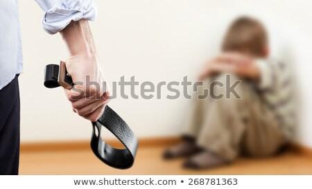 angry man raised hand holding leather belt over wall corner sitt stock photo © ia_64