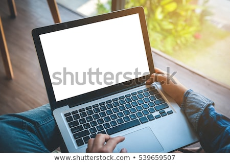 A young man is sitting with a phone in his hands at a table in the office. Stock photo © Traimak
