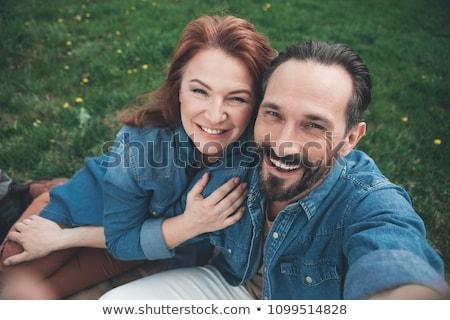 Fotó kaukázusi pár férfi nő mosolyog ül Stock fotó © deandrobot