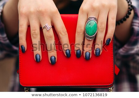 Unrecognizable woman with dark nails holding red handbag. Stock photo © studiolucky