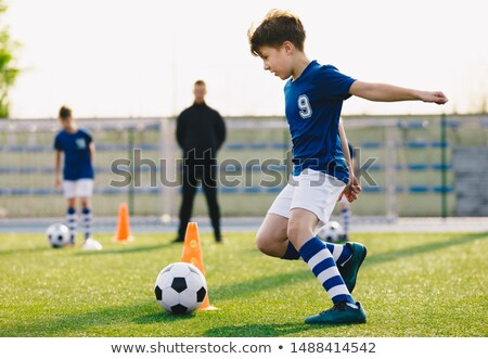 Soccer camp for kids. Boys practice dribbling in a field. Players develop good soccer dribbling skil Stock photo © matimix