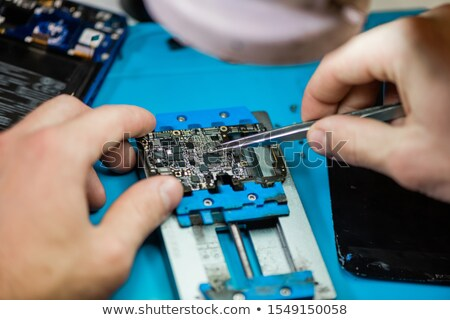 Tweezers in hands of professional repairman during work with tiny details Stock photo © pressmaster