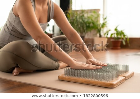 Active female sitting on the floor with crossed legs during yoga exercise Stock photo © pressmaster