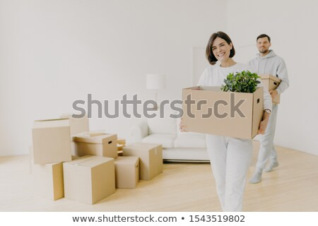 Happy woman and her husband carry boxes with personal belongings, being busy during relocation in ot Stock photo © vkstudio