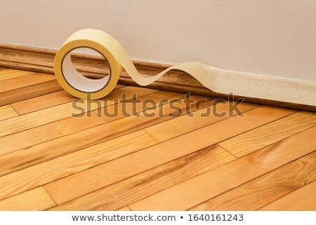 Sticking masking tape to the baseboard Stock photo © Kotenko