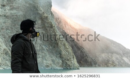 Young man tourist makes a selfie standing at the edge of the crater of the Ijen volcano or Kawah Ije Stock photo © galitskaya