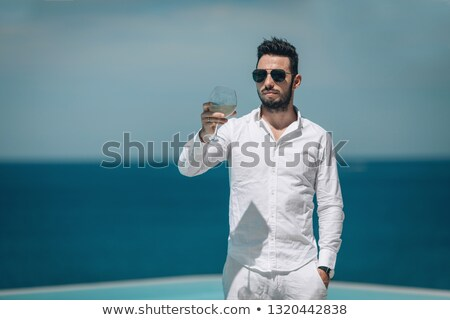 Handsome young man in sunglasses sitting with drink on summer terrace  Stock photo © Nejron