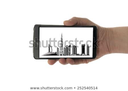 Női kéz mobiltelefon Dubai sziluett izolált Stock fotó © compuinfoto