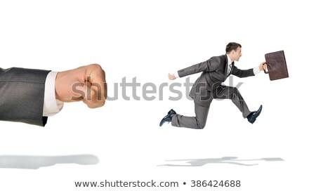Businessman runaway from big fist Stock photo © cherezoff