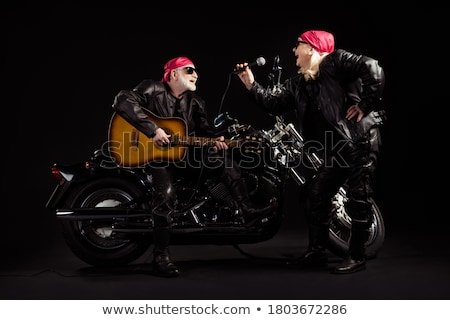 mature man in leather jacket playing guitar stock photo © feedough