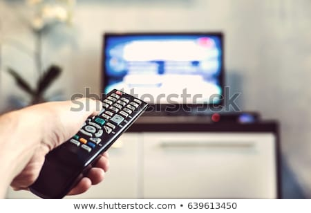 Man pushing button on remote control Stock photo © deandrobot