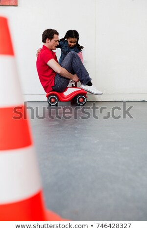 young girl teaching man to ride toy car stock photo © is2
