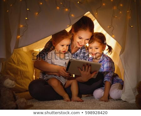 family with tablet pc in bed at night at home stock photo © dolgachov