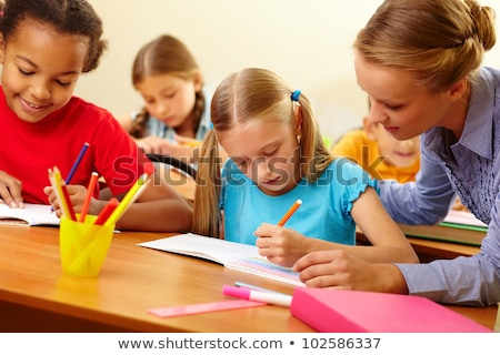 Young female teacher teaching schoolkid at desk in classroom of elementary school Stock photo © wavebreak_media