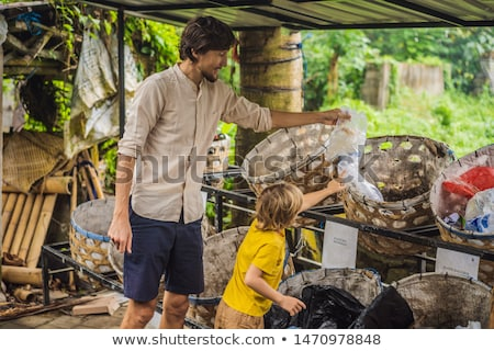 Dad and son, separate garbage collection. Teaching children to separate garbage collection Stock photo © galitskaya