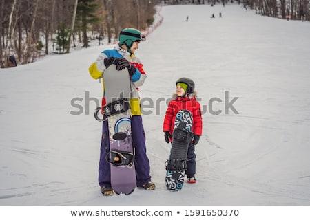 Snowboard instructor teaches a boy to snowboarding. Activities for children in winter. Children's wi Stock photo © galitskaya