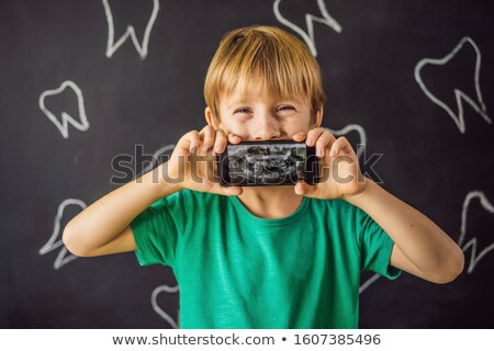 The boy shows his X-ray image of his teeth with an abnormally strange extra tooth. Children's dentis Stock photo © galitskaya