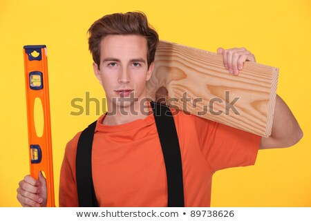 junior carpenter posing with ruler and lumber over shoulder Stock photo © photography33