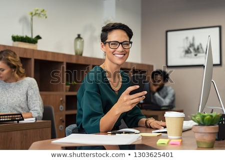 Portrait of business woman using phone and computer at desk Stock photo © wavebreak_media