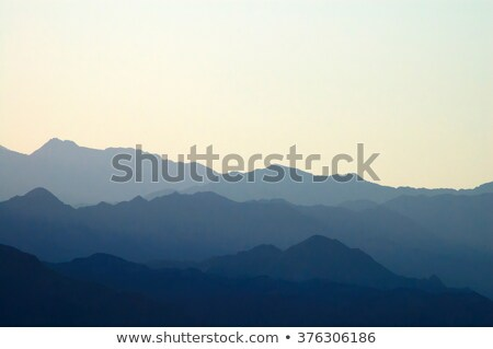 Stock photo: Silhouettes of cloudy mountains in evening