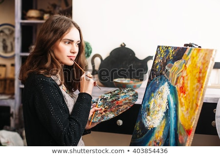 beautiful pensive young woman painter holding paintbrushes in art studio stock photo © deandrobot