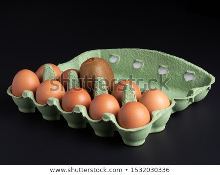 Stock photo: One egg in a row of kiwis. White background. Concept.