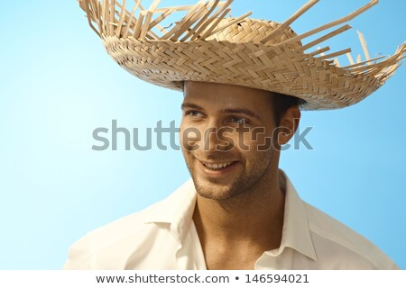 portrait of a cheerful young man in straw hat stock photo © deandrobot