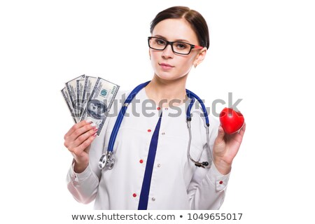 young beautiful female doctor holding heart and money in her hands on white background stock photo © traimak