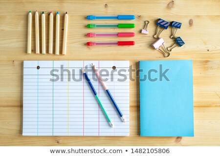 Sets of pens and crayons, clips, book in blue cover and lined notebook page Stock photo © pressmaster