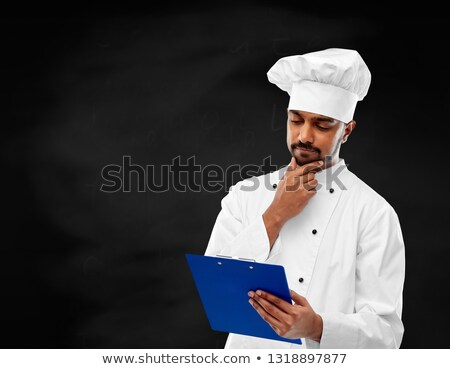 chef reading menu on clipboard over chalkboard Stock photo © dolgachov