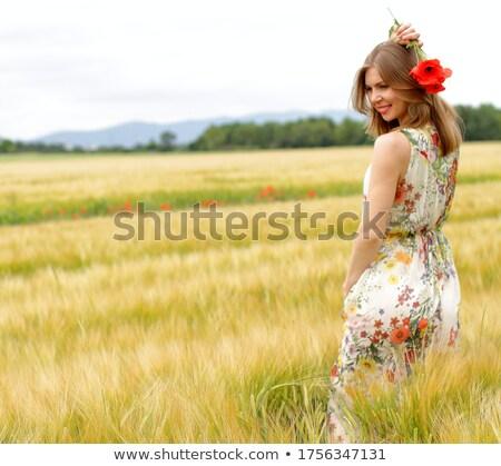 happy girl in a yellow dress staying in the field of flowering rape. Nature blooms rape seed field Stock photo © ElenaBatkova