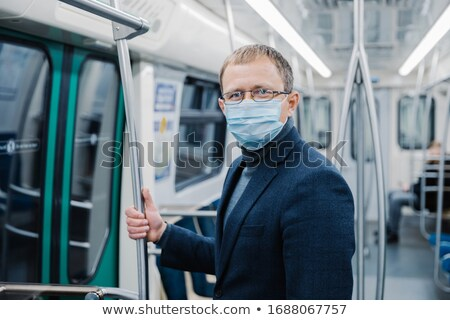 Shot of young man wears spectacles and protective face mask to prevent spreading coronavirus disease Stock photo © vkstudio
