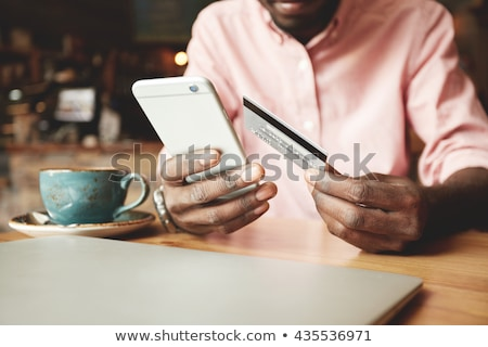 Image of man holding credit card while making payment online wit Stock photo © deandrobot
