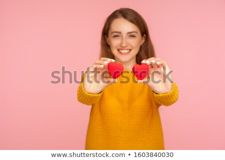 Lovely girl in sweater with toy heart. stock photo © Massonforstock