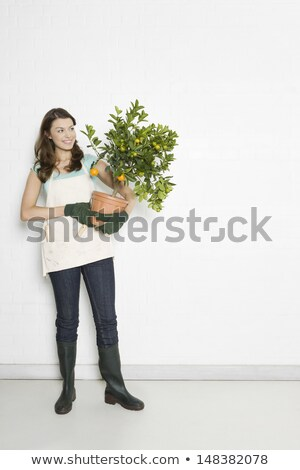 Attractive woman holding an orange while standing against a white background stock photo © wavebreak_media