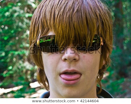 young boy with red long hair and sunglasses pocks his tongue and Stock photo © meinzahn