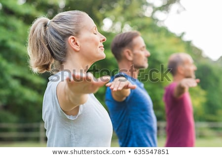 woman doing stretching yoga exercises outdoors stock photo © restyler