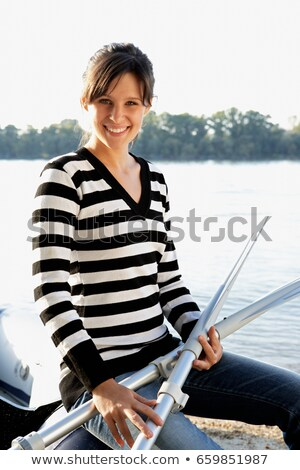 Woman leaning on a raft holding two oars Stock photo © IS2