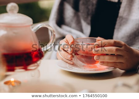 Beautiful young girl holding a glass in her hand with coffee and typing text on the keyboard, sittin Stock photo © Traimak
