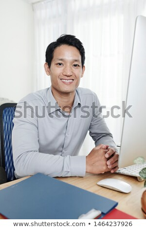 A man is sitting at a table in the office and looks at the graph on a magnetic board. Stock photo © Traimak