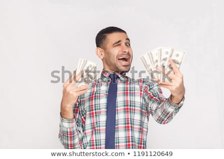 Happy businessman standing isolated holding money and credit card. Stock photo © deandrobot