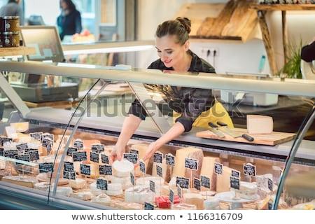 Shop clerk woman sorting cheese in the supermarket display Stock photo © Kzenon